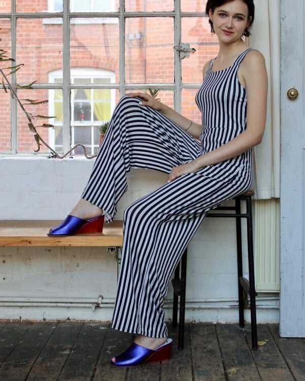 Marla in Ops&Ops No15 Metallic Purple wedge mules worn with striped, strappy jumpsuit