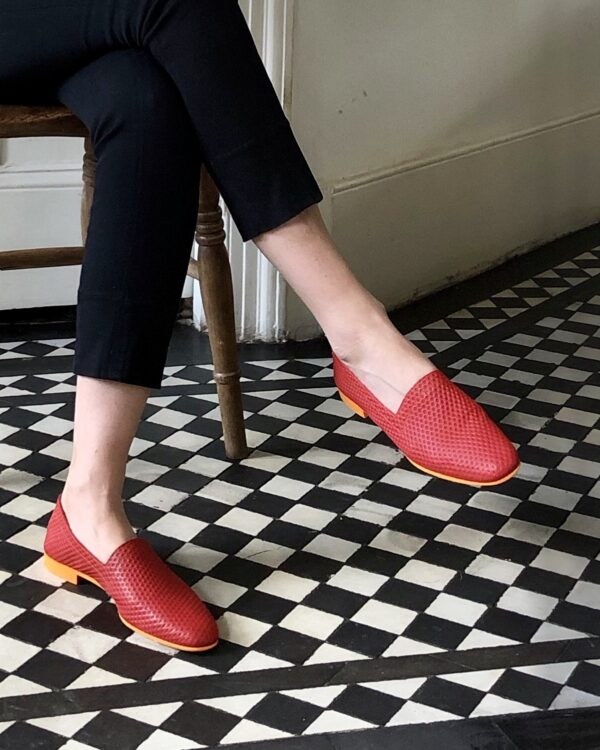 Ops&Ops No10 Action Red flats with orange sole and heel worn with capri pants on black and white tiled floor