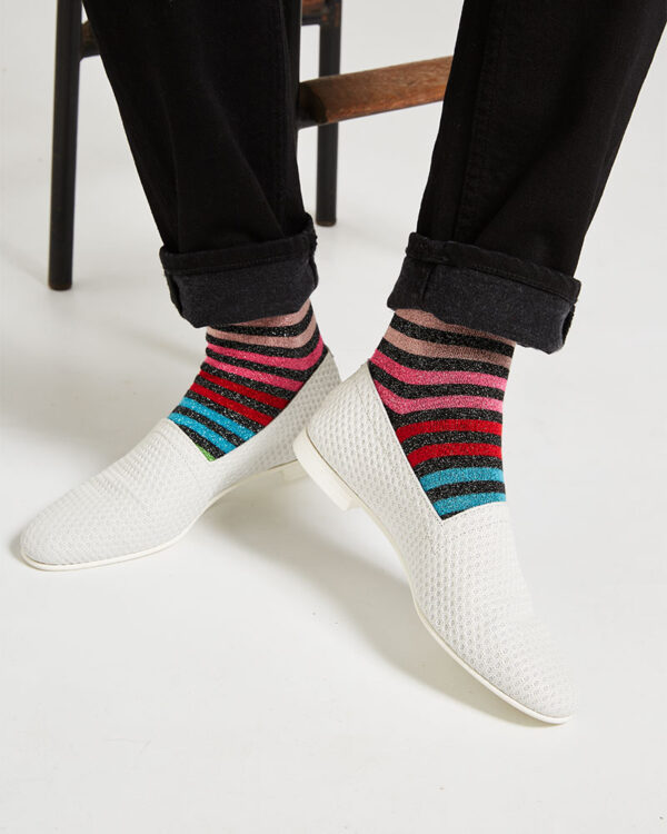 Ops&Ops No10 Action White leather flats close-up worn with multi-striped lurex socks and black turned-up jeans